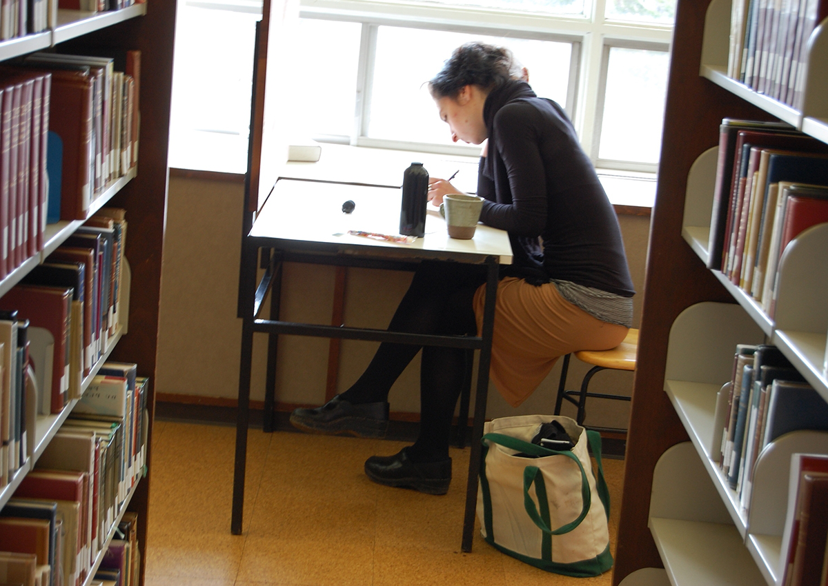 female student at desk in library studying